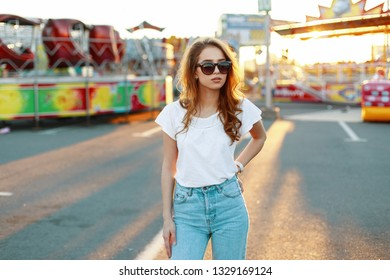 Redhead stylish young hipster woman in white fashionable in vintage jeans in trendy sunglasses in an amusement park. Pretty girl fashion model enjoys sunny weekend.