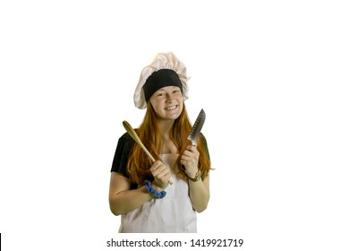 Redhead teen chef with knife and wooden spoon smiling in chef hat and apron isolated on white with copyspace.