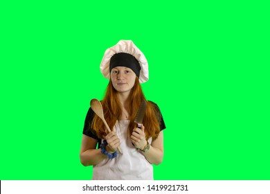 Redhead teen chef with knife and wooden spoon in chef hat and apron isolated on green with copy space.