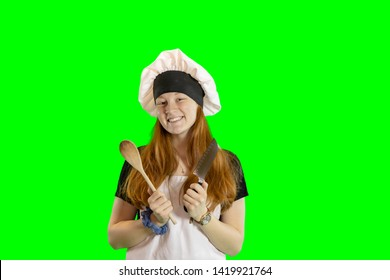 Redhead teen chef with knife and wooden spoon smiling in chef hat and apron isolated on green with copy space.