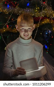 Redhead teen holding in his hand the glowing box
