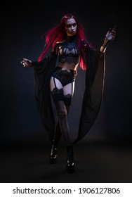 Redhead vampire woman posing on black background in lace lingerie and heels. Studio portrait