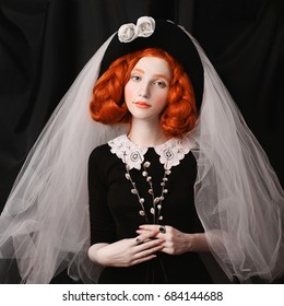 Redhead victorian woman with long braids with an unusual appearance in a black dress with a cap and veil on her head. Lovely girl with pale skin and rings with stones on a black background.