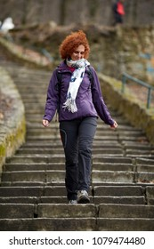 Redhead woman with backpack taking a walk in the park
