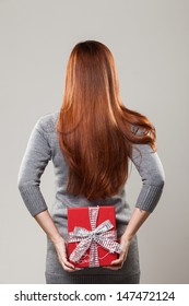 Redhead woman with beautiful long straight hair hiding a decorative red Christmas or Valentine gift behind her back as she prepares to surprise a loved one