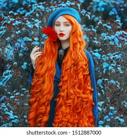 Redhead woman in blue coat on flower background. Fashion model with long red hair with red flower in hand. turban and stylish coat. Red lips and blue eyes. Colored nails. Beauty portrait. Wavy hair