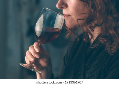 Redhead woman in a celebration party tasting luxury red wine from glass; color photo.