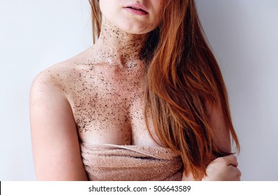 Redhead woman cleans skin shoulder and neck with coffee scrub