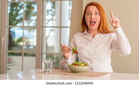 Redhead woman eating fresh green salad at home surprised with an idea or question pointing finger with happy face, number one