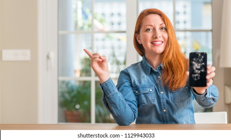 Redhead woman holding broken smartphone very happy pointing with hand and finger to the side