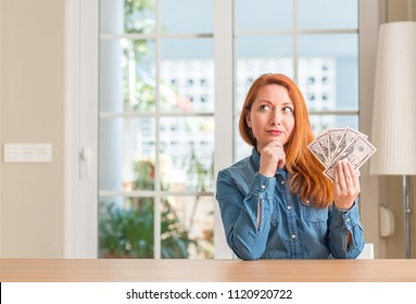 Redhead woman holding dollar bank notes at home serious face thinking about question, very confused idea