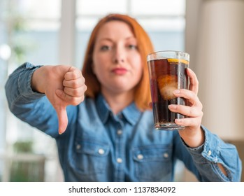 Redhead woman holding soda refreshment with angry face, negative sign showing dislike with thumbs down, rejection concept