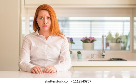 Redhead woman at kitchen skeptic and nervous, frowning upset because of problem. Negative person.
