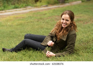 Redhead woman lie on the grass in the autumn park