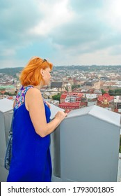 Redhead woman looking at city Lviv panorama from tower in Ukraine. Tourist with curly hair walking on lookout tower in town