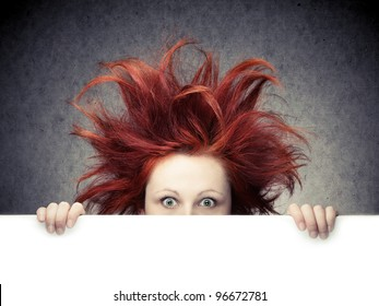 Redhead woman with messy hair against gray background