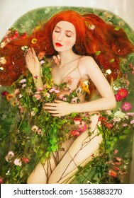 Redhead woman in new ceramic bathroom. Water with flower essential. Valentine's Day bath. Aromatherapy with flower petals. Take bath. Model washing in bathroom. Flowers float in water. Spa procedures