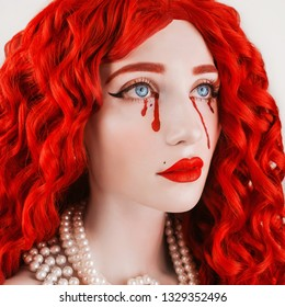 Redhead woman with pale skin and red lips. Girl with blood tears. Red curly wig. Redhead woman portrait with beads on neck. Red tears on skin. Long wavy wig. Big beautiful blue eyes. Eva girl
