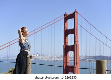 Redhead woman posing by Golden Gate Bridge