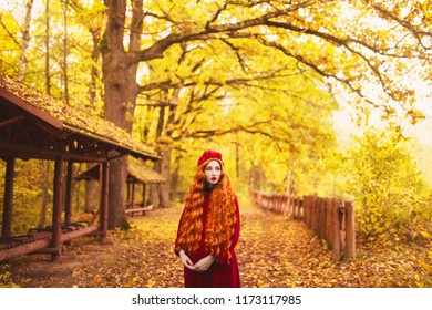 Redhead woman in red coat on picturesque autumn background. Picturesque september landscape. Girl on background of forest with orange autumn leaves.
