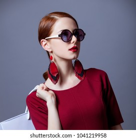Redhead woman i red dress with shopping bags on grey background