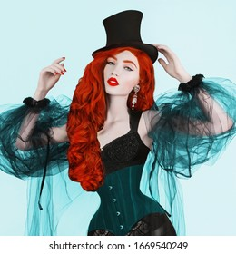 Redhead woman with red lips in black top hat. Girl with red hair and pale skin. Redhead woman in black fetish corset. Long wavy wig. Voluminous hair. Retro lady in vintage fetish clothes. Retro corset