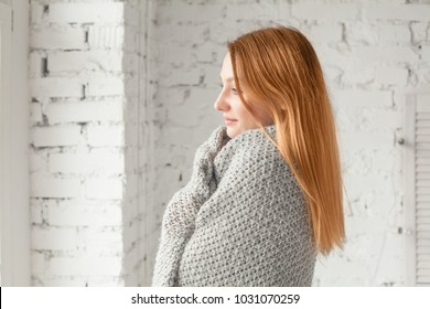 Redhead Woman Relaxing at Home in Cozy Winter or Autumn Weekend with Grey Knitted Plaid