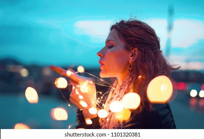 Redhead woman sending kiss with fairy light garland at evening, outdoors