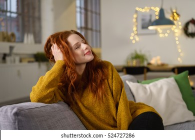 redhead woman sitting at home in winter holidays leaning her head on her hand