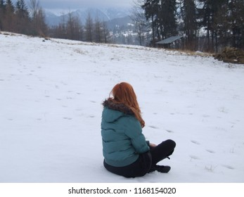 Redhead woman sitting on the snow and looking at the mountains in the background. Girl with ginger hair relaxing in winter season after hiking to the top peak.