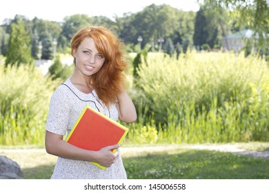 Redhead woman standing in park near university, college with books on nature in summer or spring. Happy smiling beautiful young girl university student