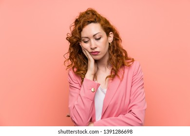Redhead woman in suit over isolated pink wall unhappy and frustrated