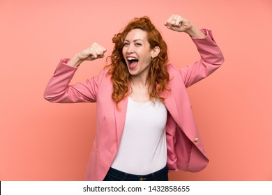Redhead woman in suit over isolated pink wall celebrating a victory