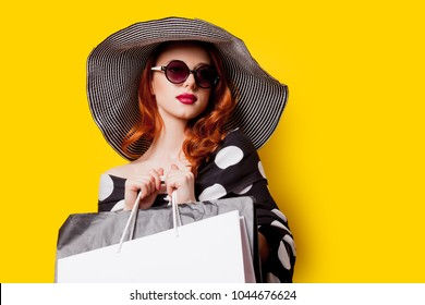 Redhead woman in sunglasses with shopping bags on yellow background