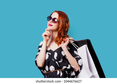 Redhead woman in sunglasses with shopping bags on blue background