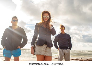 Redhead woman in sunglasses and two mans over bright summer sky.