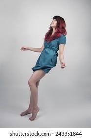 Redhead woman in a teal dress falling