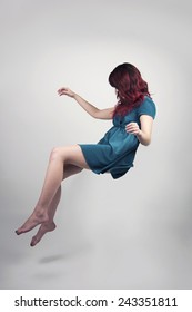 Redhead woman in a teal dress floating