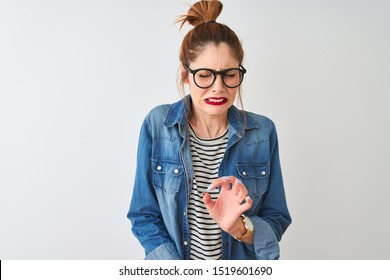 Redhead woman wearing striped t-shirt denim shirt and glasses over isolated white background disgusted expression, displeased and fearful doing disgust face because aversion reaction