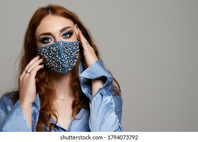 Redhead woman wearing stylish blue protective face mask with pearls, rhinestones, beads. Fashion accessory during quarantine of coronavirus. Close up studio portrait. Copy, empty space for text