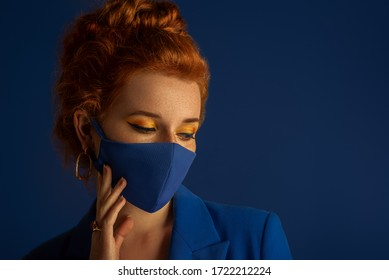 Redhead woman wearing trendy fashion blue monochrome outfit with luxury designer protective face mask. Model has matching bold eyes makeup. Vogue, style during quarantine of coronavirus outbreak.