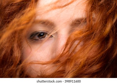 Redhead Woman's Eye Close Up with Blurred Hair