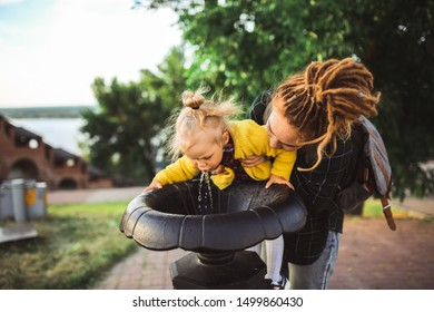 redhead young caucasian mom hipster with dreadlocks and toddler girl drink from a fountain for a drink in public park, family walks in the city. The concept of care and motherhood,
