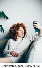 Redhead young woman with curly hair, in earphones, looks at smart phone screen, sitting on sofa and communicating online by video chat (toned image, selective focus)