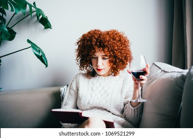 Redhead young woman with curly hair, sitting on sofa, reading a book and drinks red wine (toned image, selective focus)