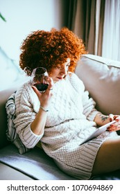 Redhead young woman with curly hair, sitting on sofa, looking at tablet screen and drinks red wine (toned image, selective focus)