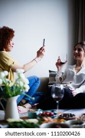 Redhead young woman with curly hair taking a photo of a friend on mobile phone, drinking red wine (selective focus)