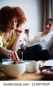 Redhead young woman with curly hair, eating appetizers and drinking red wine with a friend (selective focus)