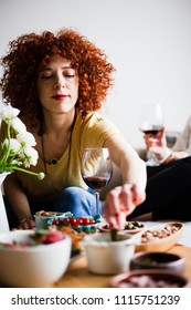 Redhead young woman with curly hair, eating appetizers and drinking red wine (selective focus)