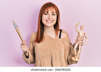 Redhead young woman holding small wooden manikin and painter brushes smiling with a happy and cool smile on face. showing teeth.